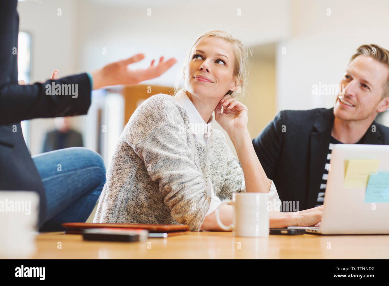 Colleagues looking at businesswoman talking while sitting on table in office - Stock Image