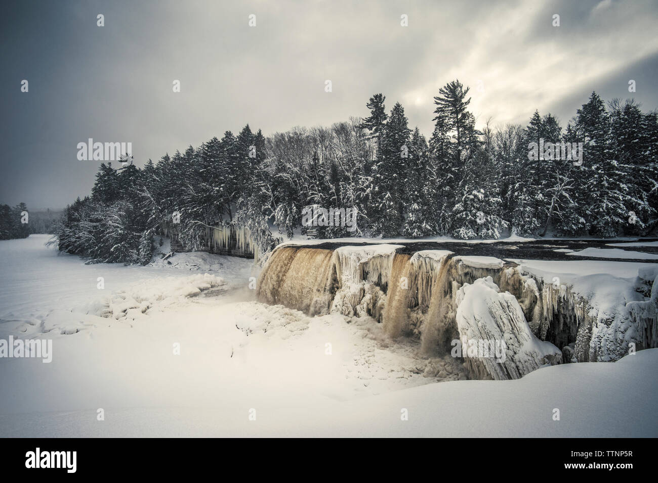 Scenic view of waterfall against cloudy sky at forest during winter - Stock Image