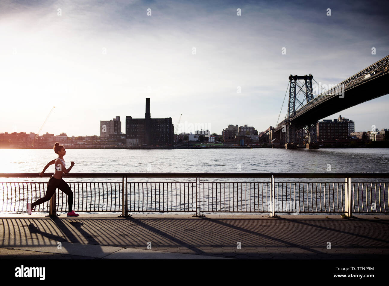 Determined woman jogging on promenade with Williamsburg Bridge in background - Stock Photo