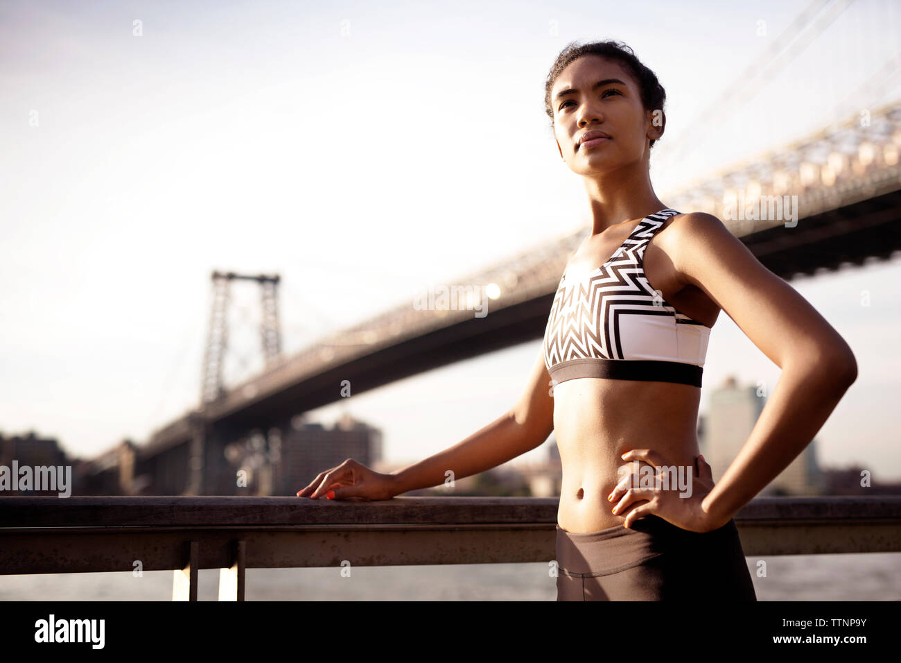 Sporty woman standing by railing against Williamsburg Bridge - Stock Photo