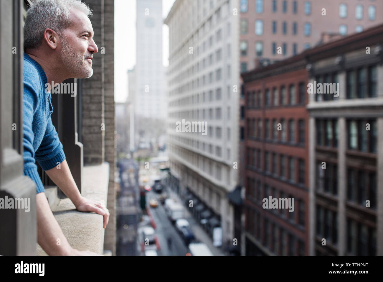Side view of man looking at buildings through window - Stock Image