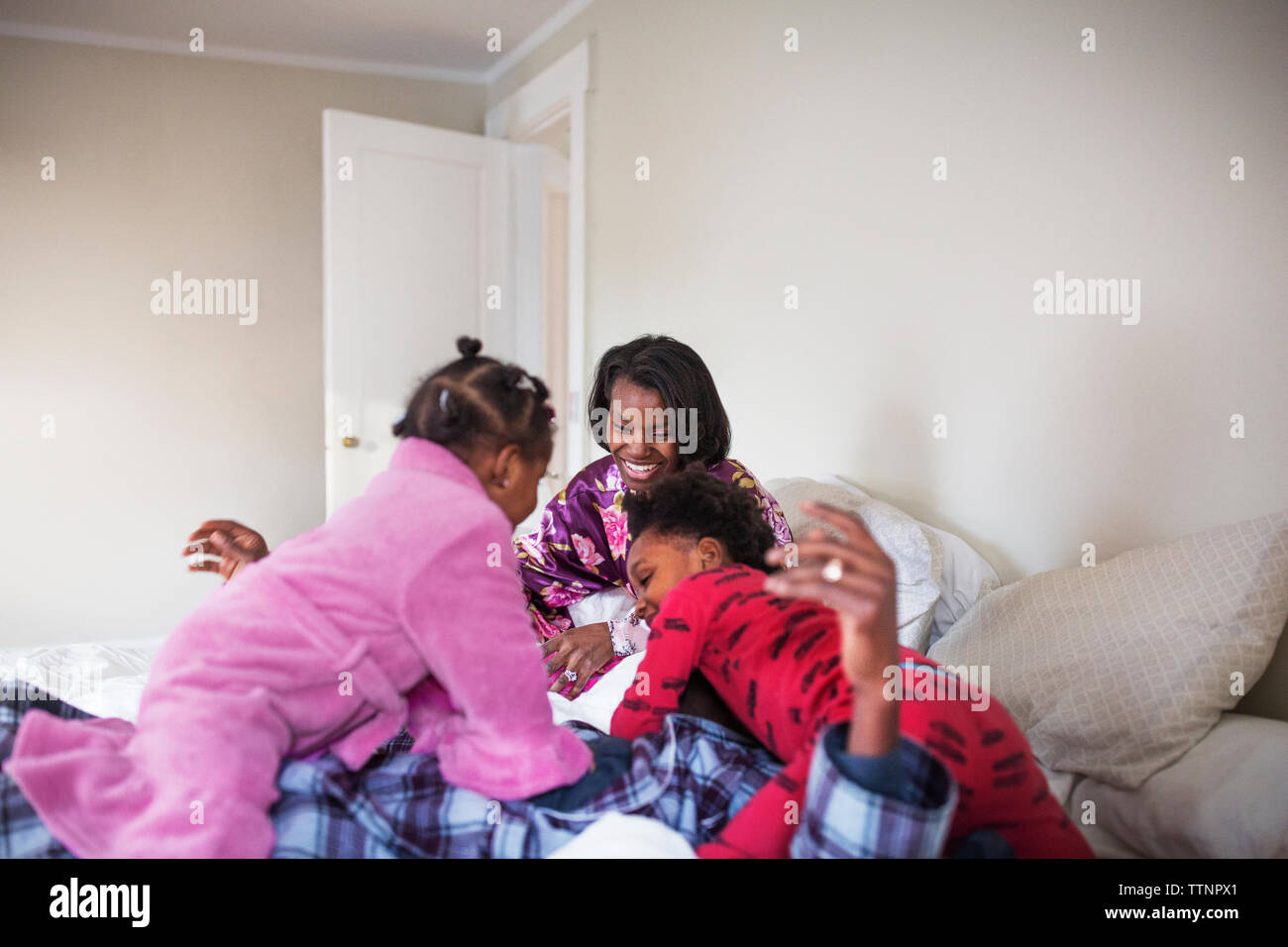 Cheerful family spending leisure time in bedroom Stock Photo