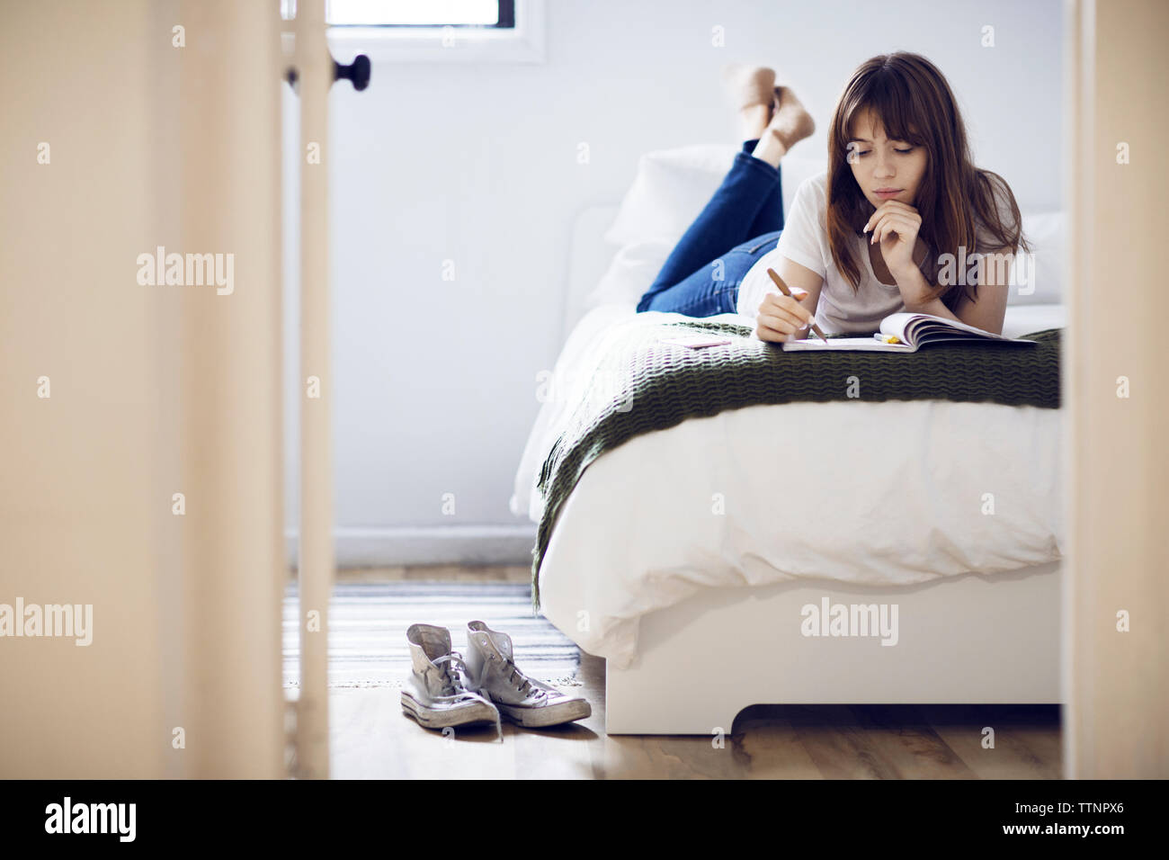 Young woman studying while lying on bed at home - Stock Image