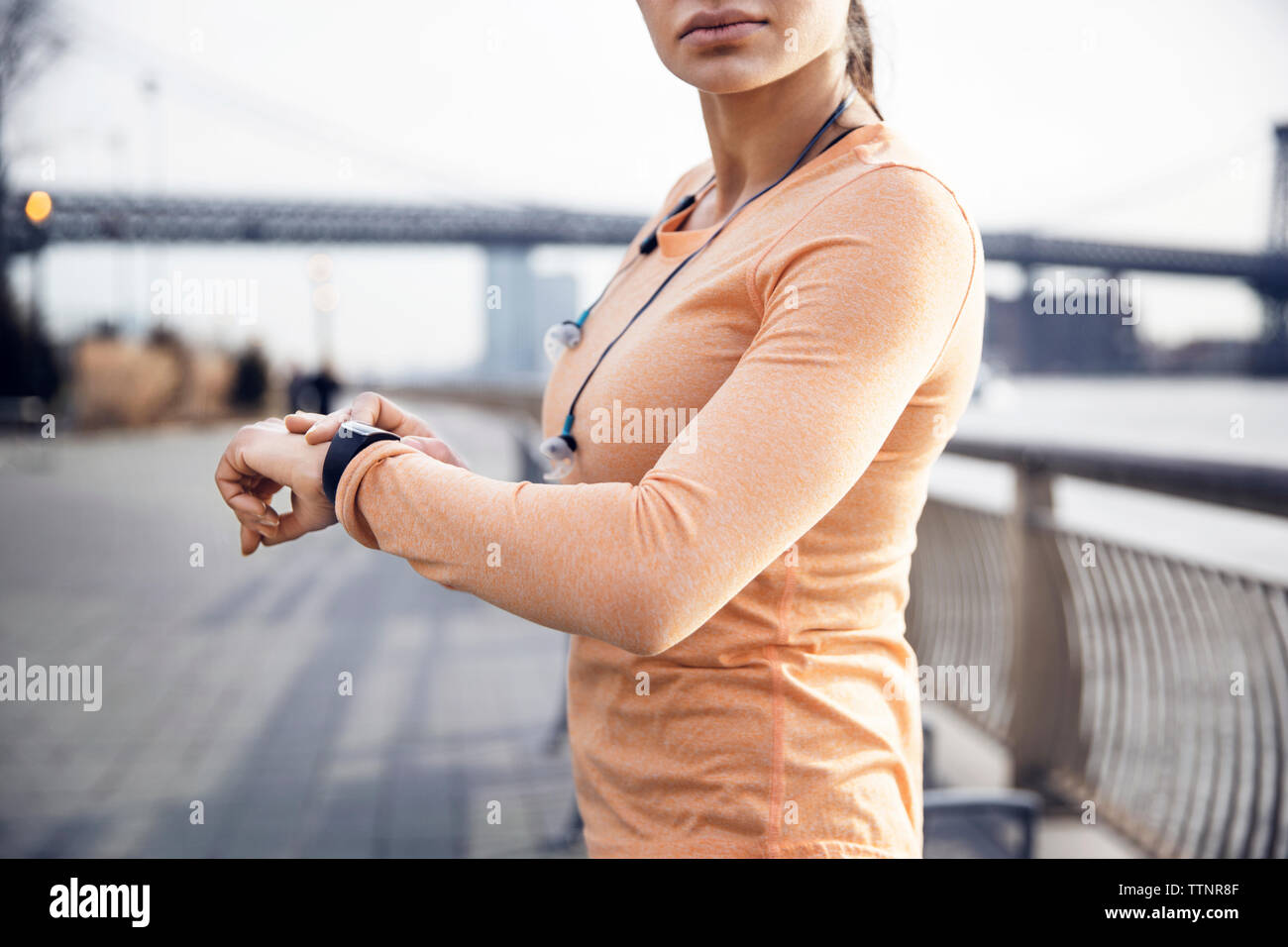 Side view of female athlete wearing smart watch on footpath with Williamsburg Bridge in background Stock Photo