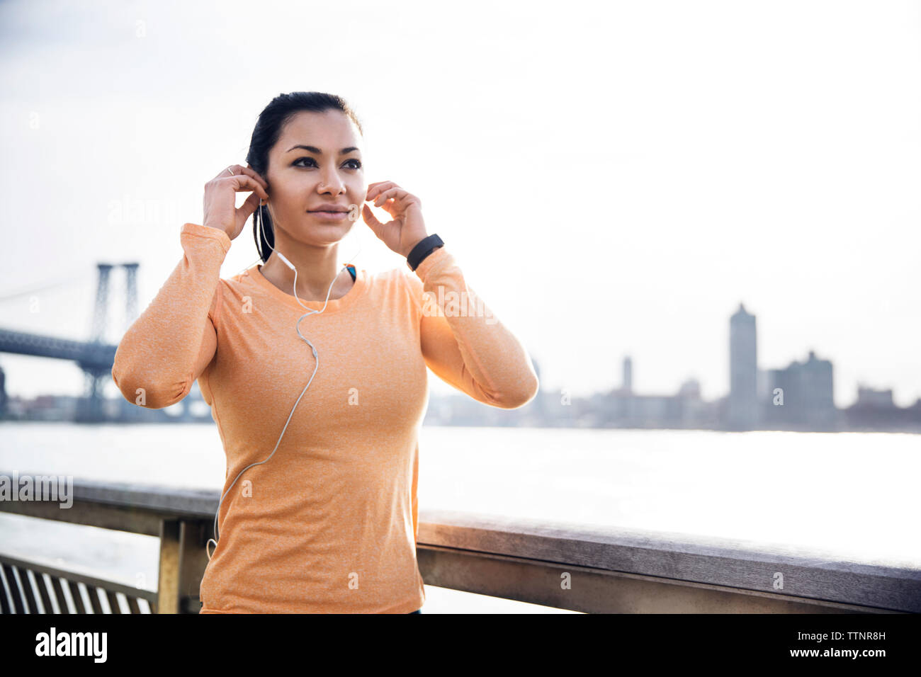Sporty female wearing earphones by river with Williamsburg Bridge in background Stock Photo