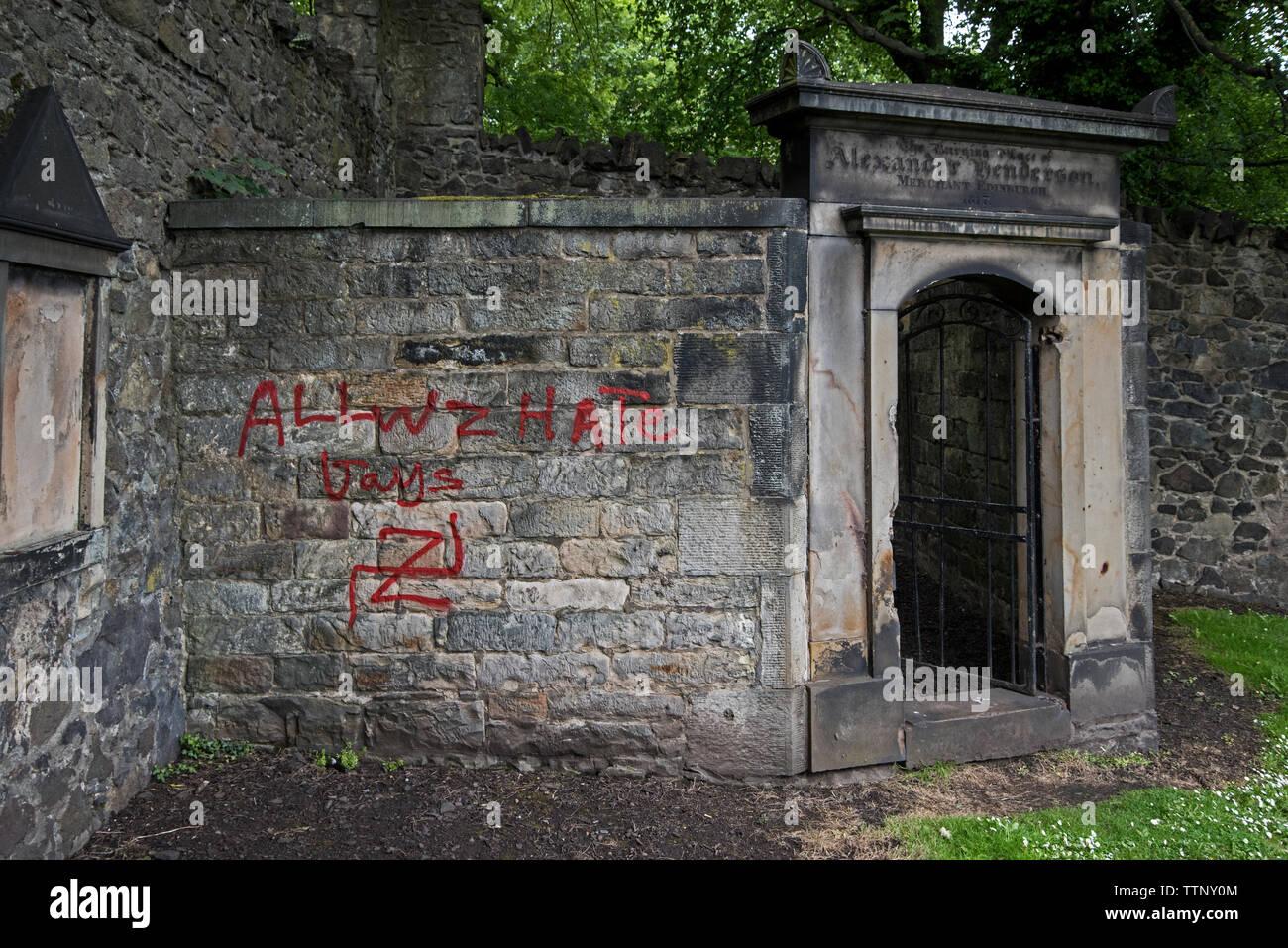 Swastikas and homophobic graffiti painted on tombs in New Calton Burial Ground, Edinburgh, Scotland, UK. June 2019. - Stock Image