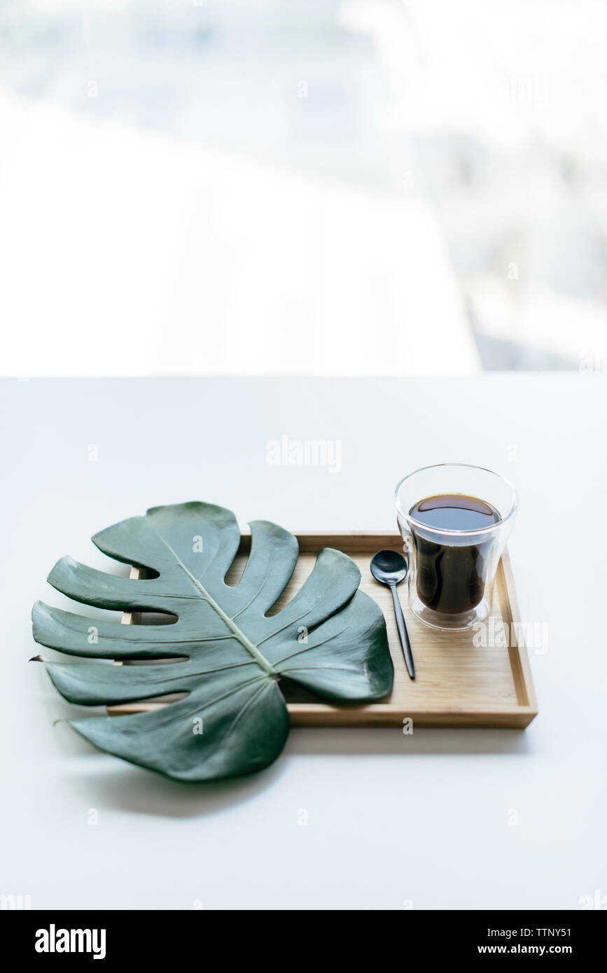 High angle view of coffee with monstera leaf in wooden tray on table - Stock Image
