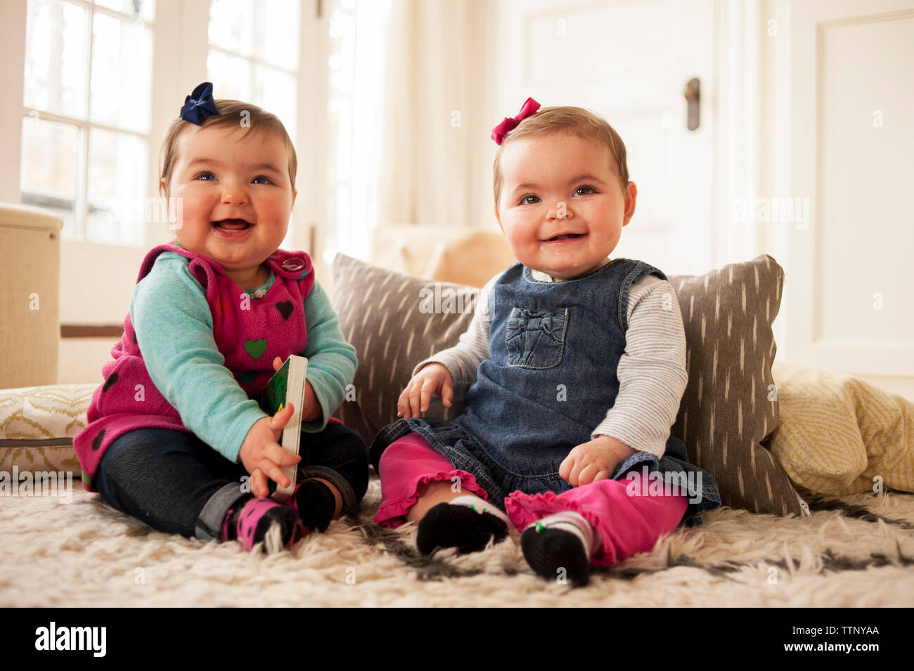 Cheerful baby girls sitting on rug at home - Stock Image