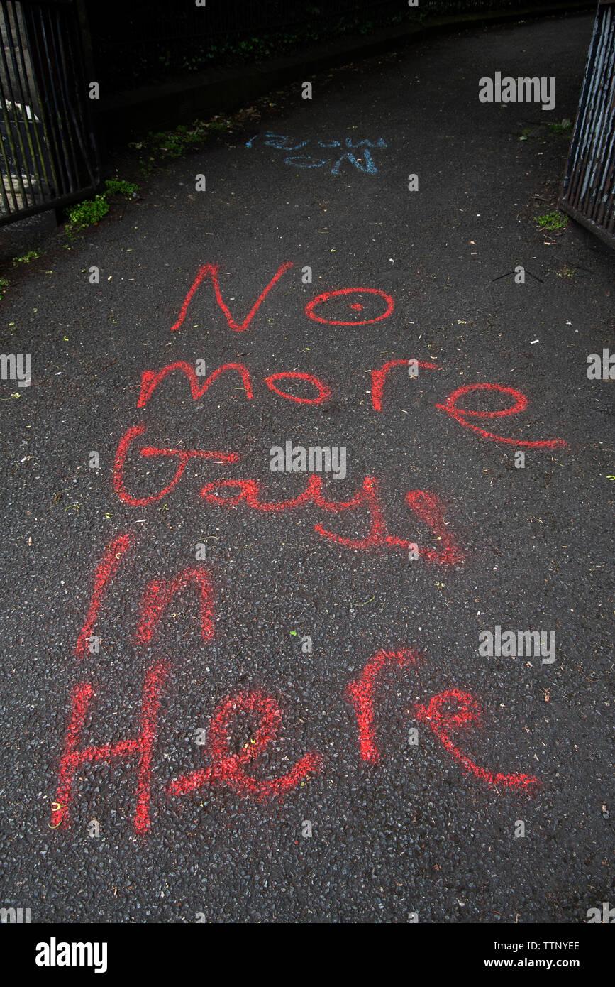 Homophobic graffiti painted at the entrance to New Calton Burial Ground, Edinburgh, Scotland, UK. June 2019. - Stock Image