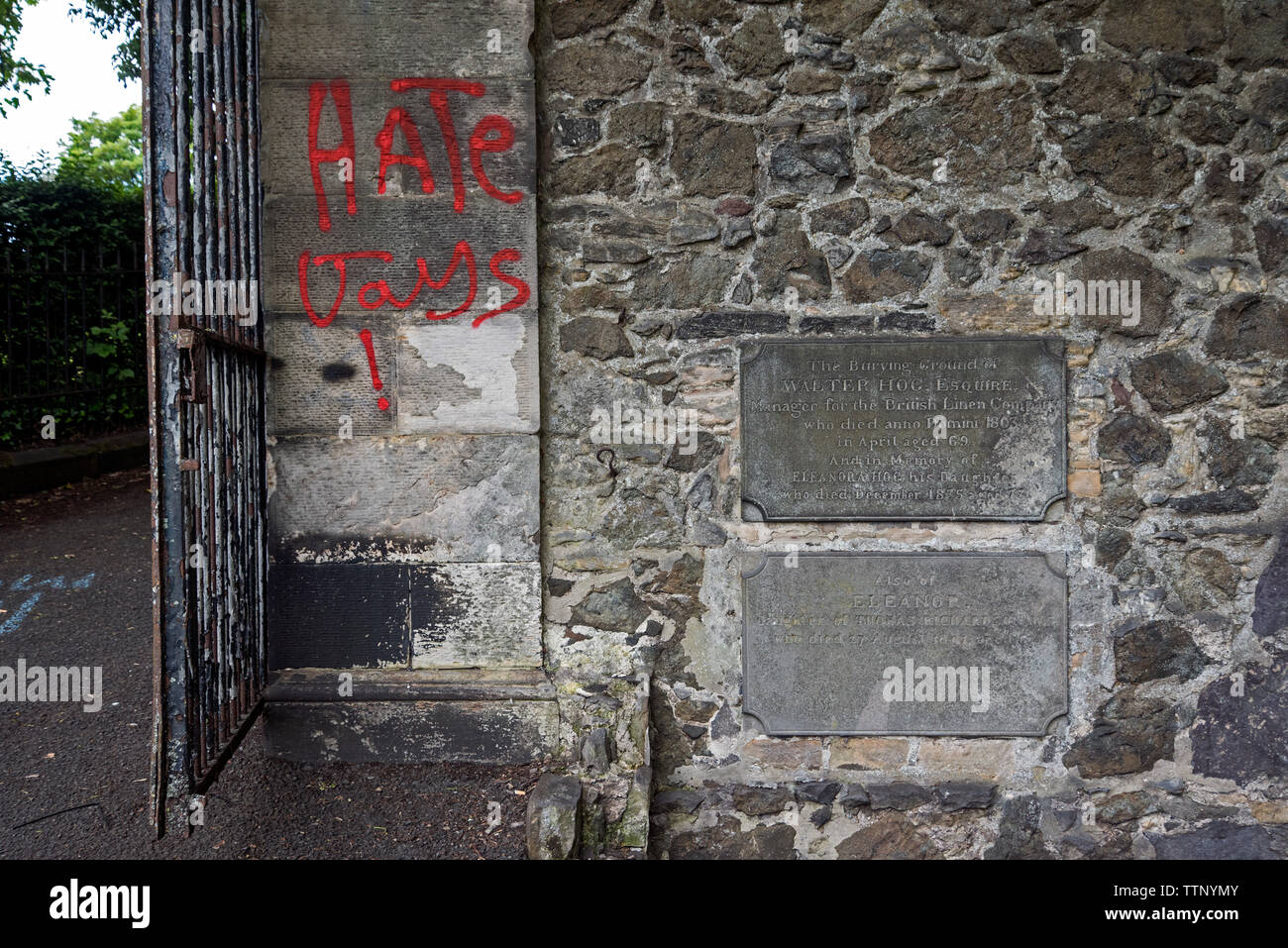 Homophobic graffiti painted on tombs in New Calton Burial Ground, Edinburgh, Scotland, UK. June 2019. - Stock Image