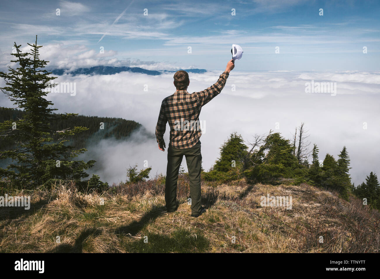 Rear view of man holding cap and standing on cliff against cloudscape Stock Photo