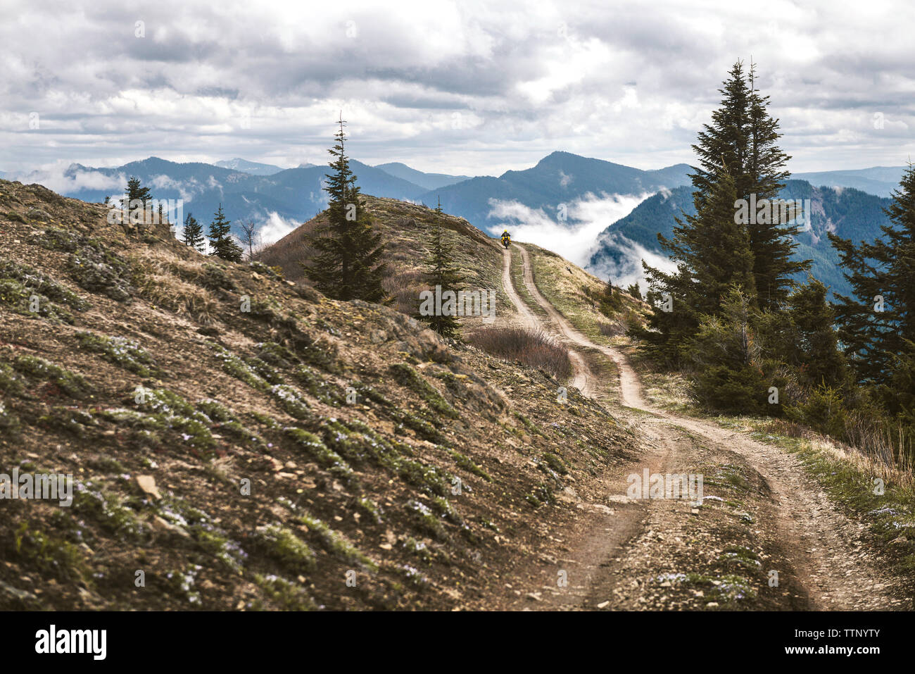 Road at mountains against cloudy sky - Stock Image
