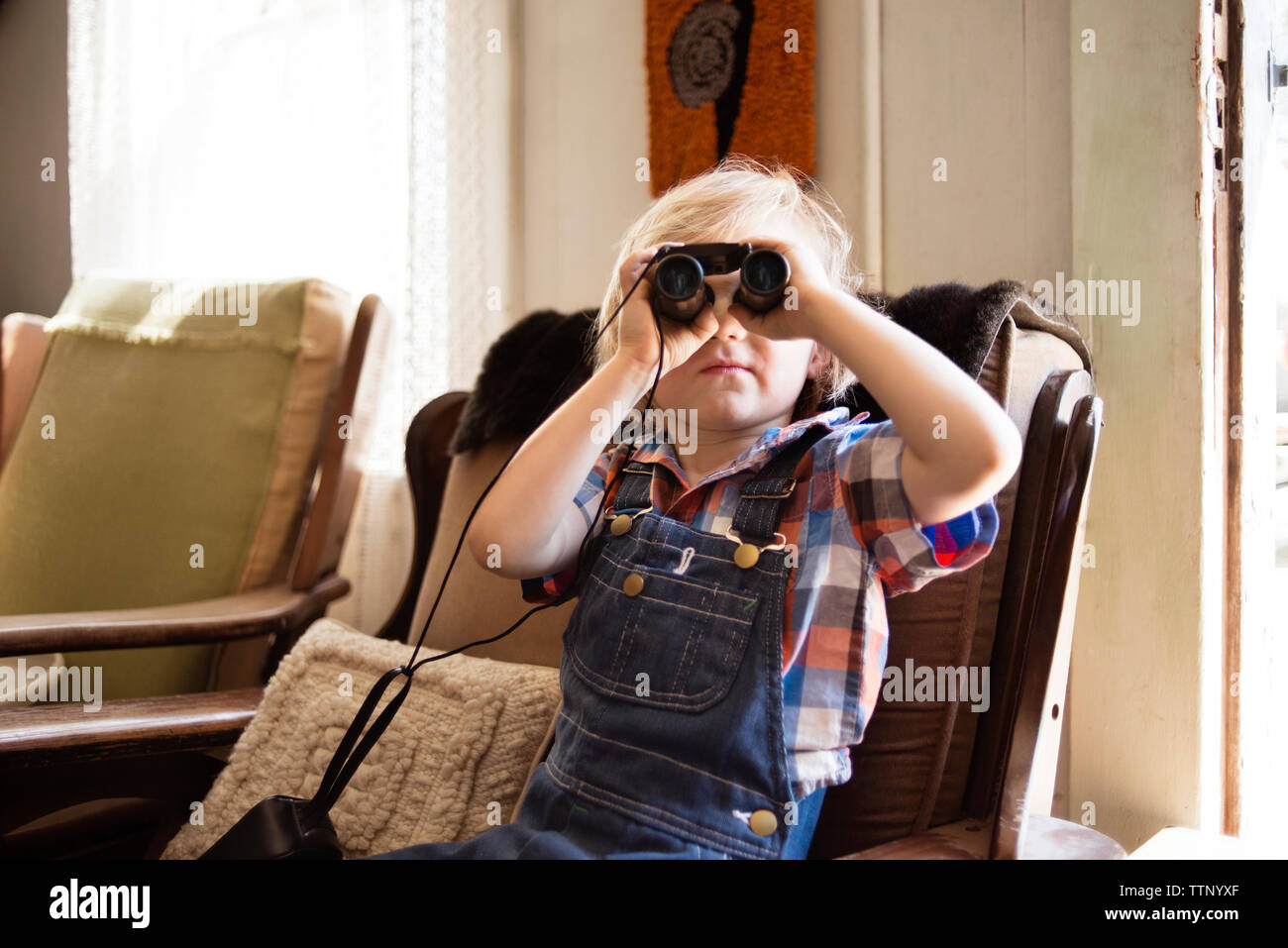 Boy looking through binoculars while sitting on chair at home - Stock Image