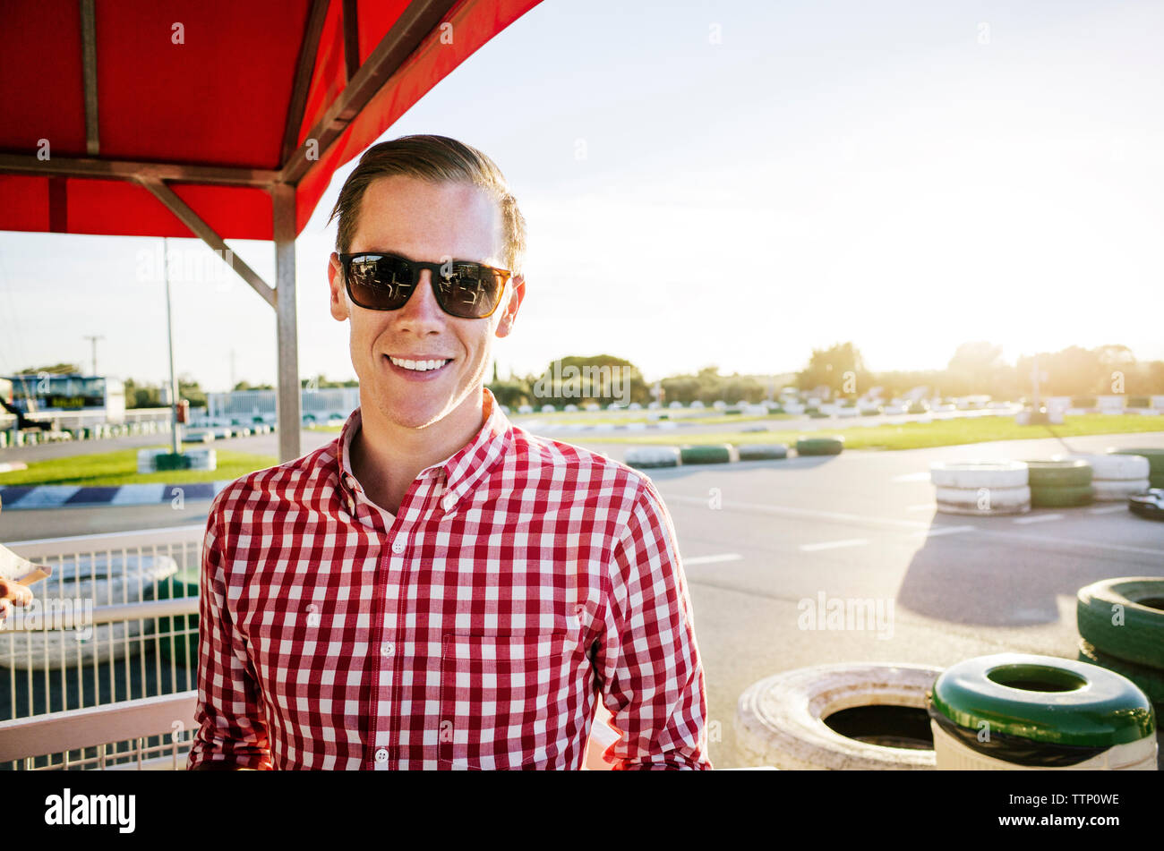 Close-up of smiling man standing at motor racing track - Stock Image