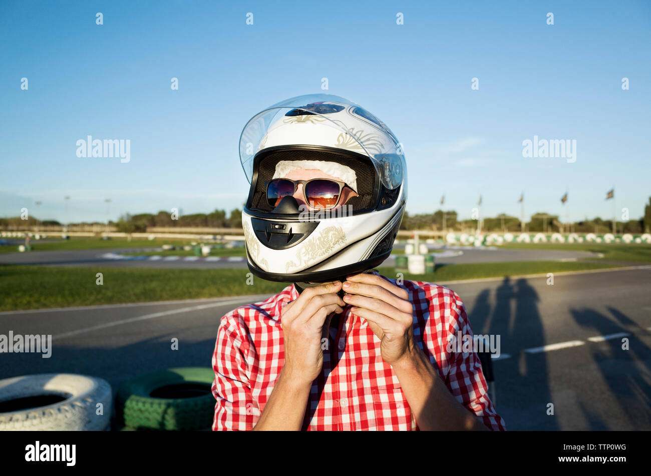 Close-up of man wearing helmet while standing at Motor Racing Track - Stock Image