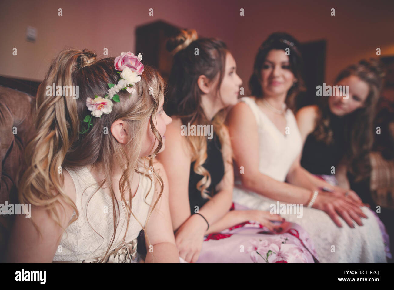 Bride with bridesmaids and flower girl sitting at home Stock Photo