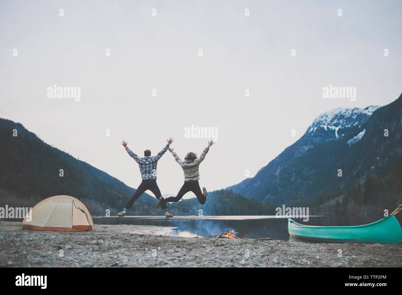 Rear view of happy young couple with arms raised jumping at lakeshore against clear sky during dusk Stock Photo
