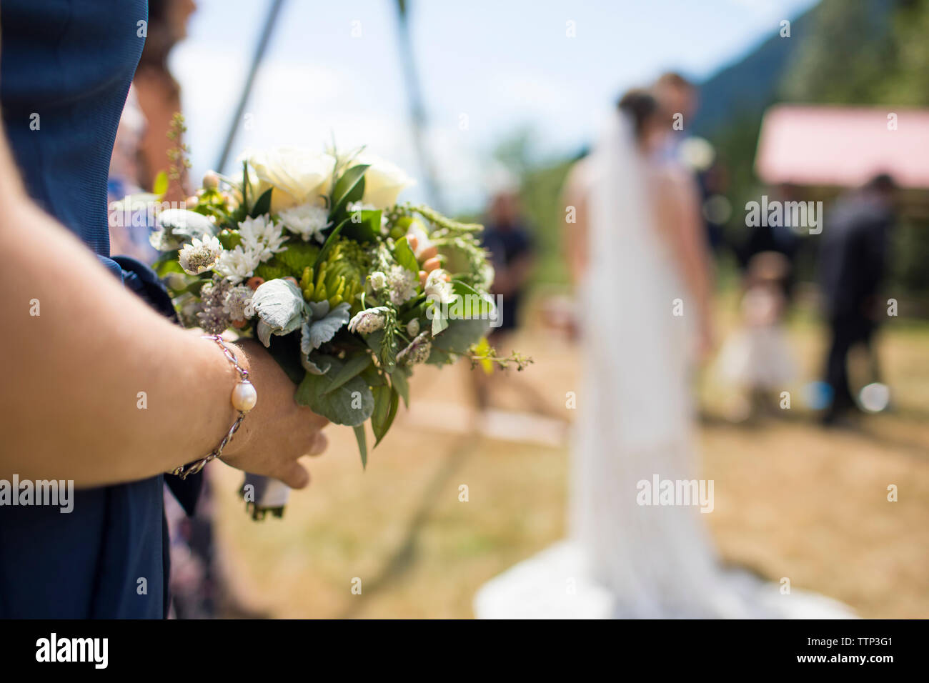 Midsection of bridesmaid holding bouquet while standing against couple in wedding ceremony - Stock Photo