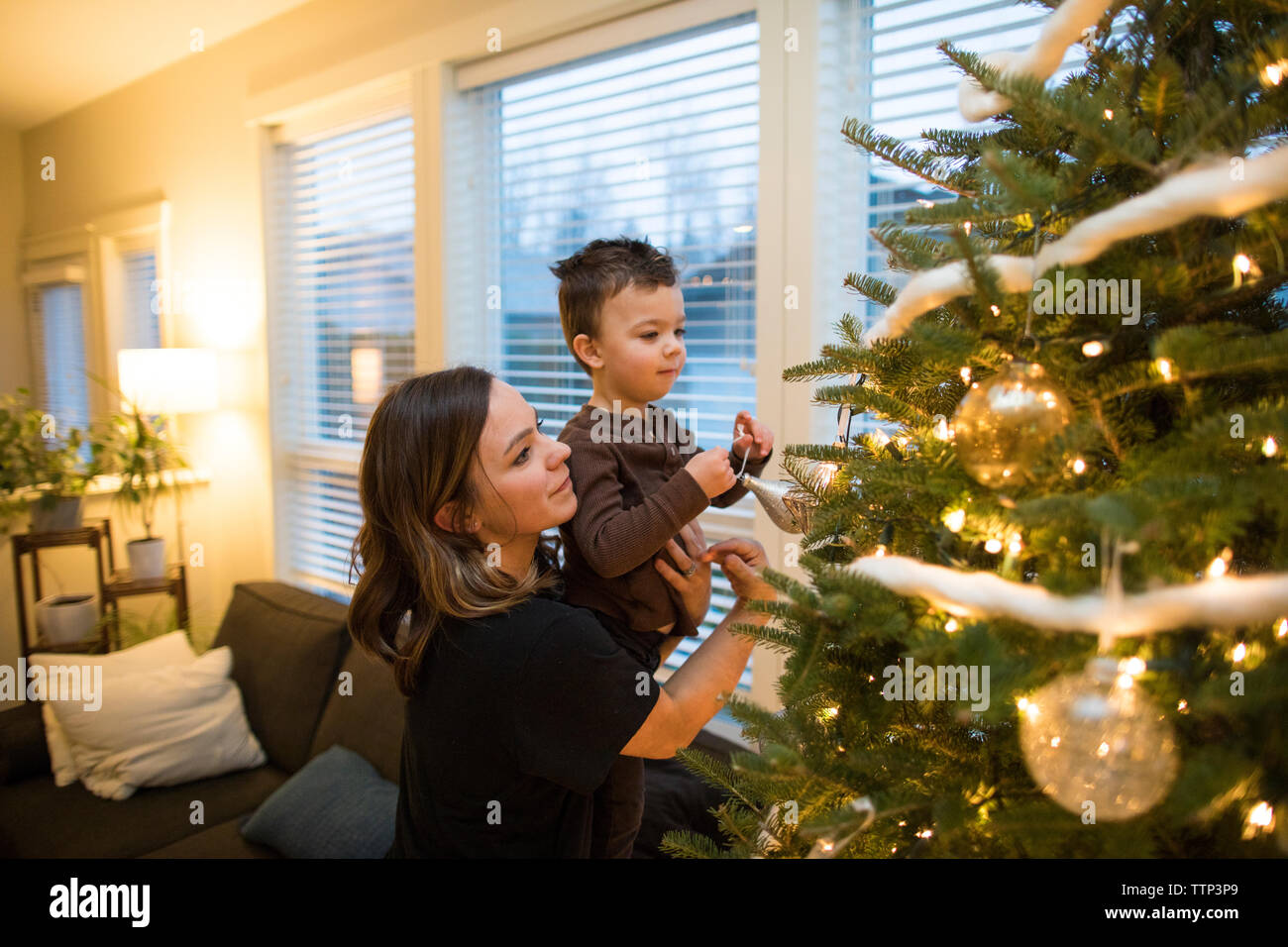 Mother and son decorate the family Christmas Tree Stock Photo