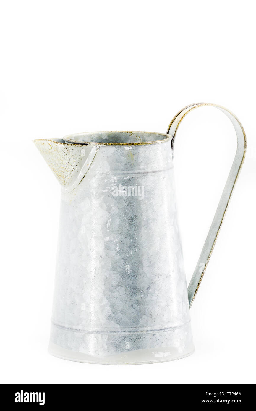An old galvanized pitcher on a white background - Stock Image
