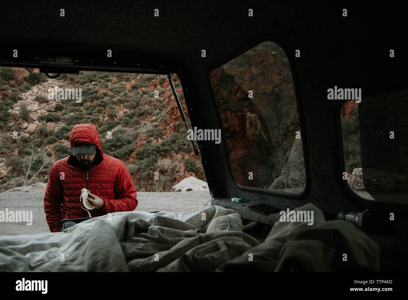 Man holding banana while standing by mini van against mountain Stock Photo