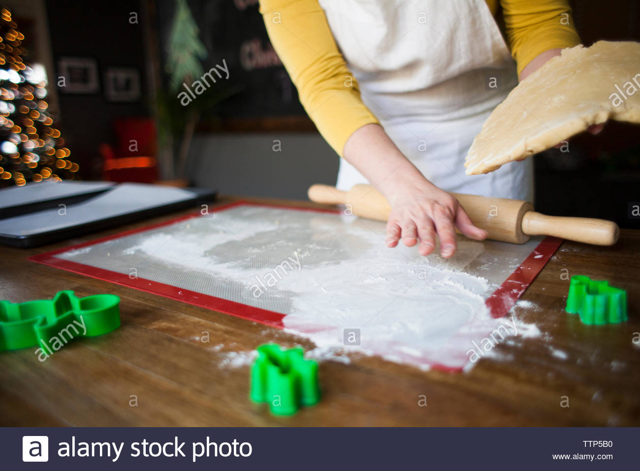 Midsection of woman making dough on kitchen counter at home - Stock Image