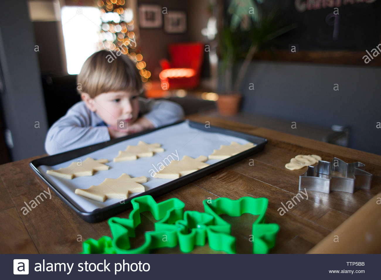 Cute boy looking away while standing by kitchen counter at home - Stock Image
