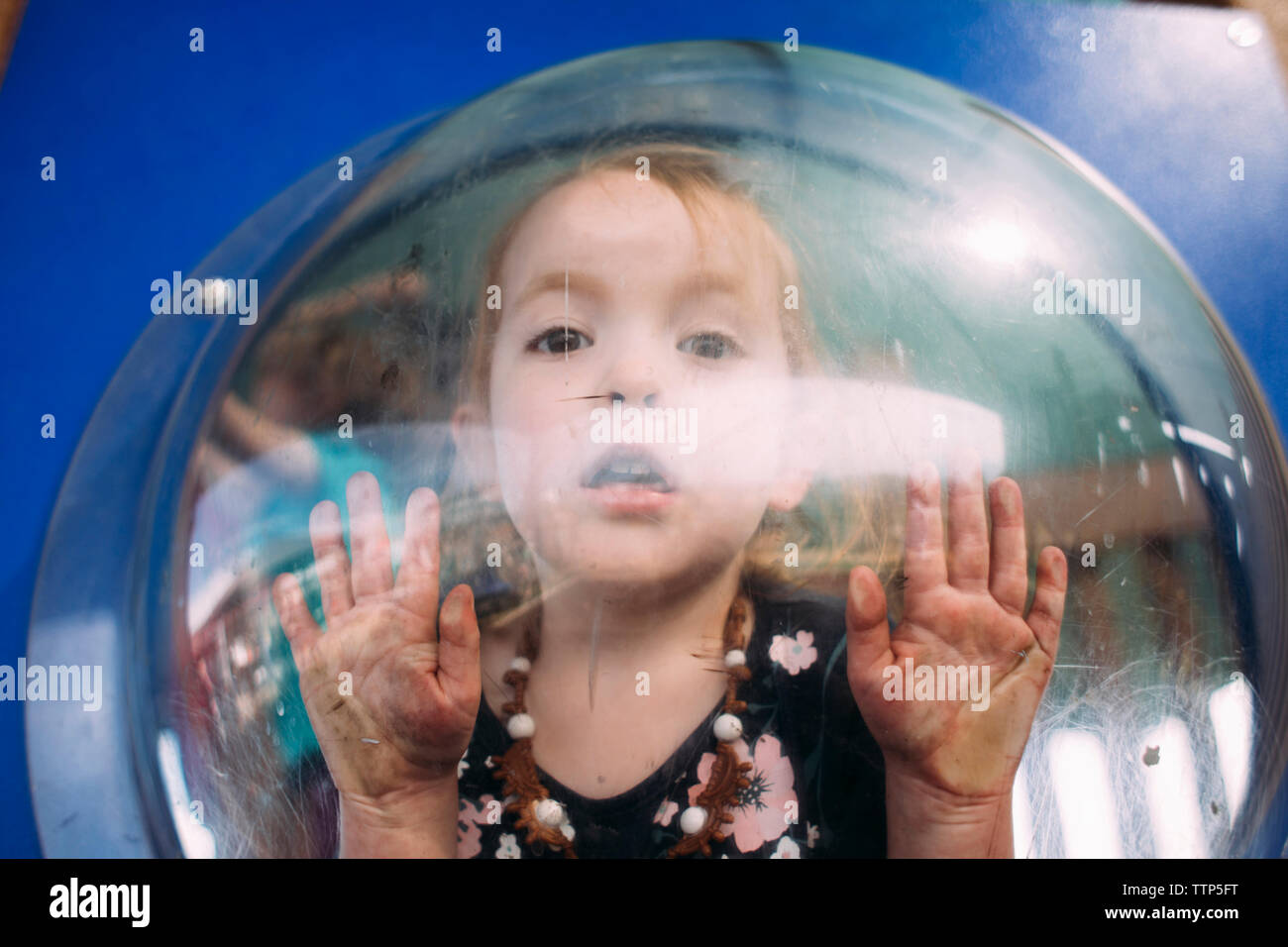 Portrait of girl looking through outdoor play equipment - Stock Image