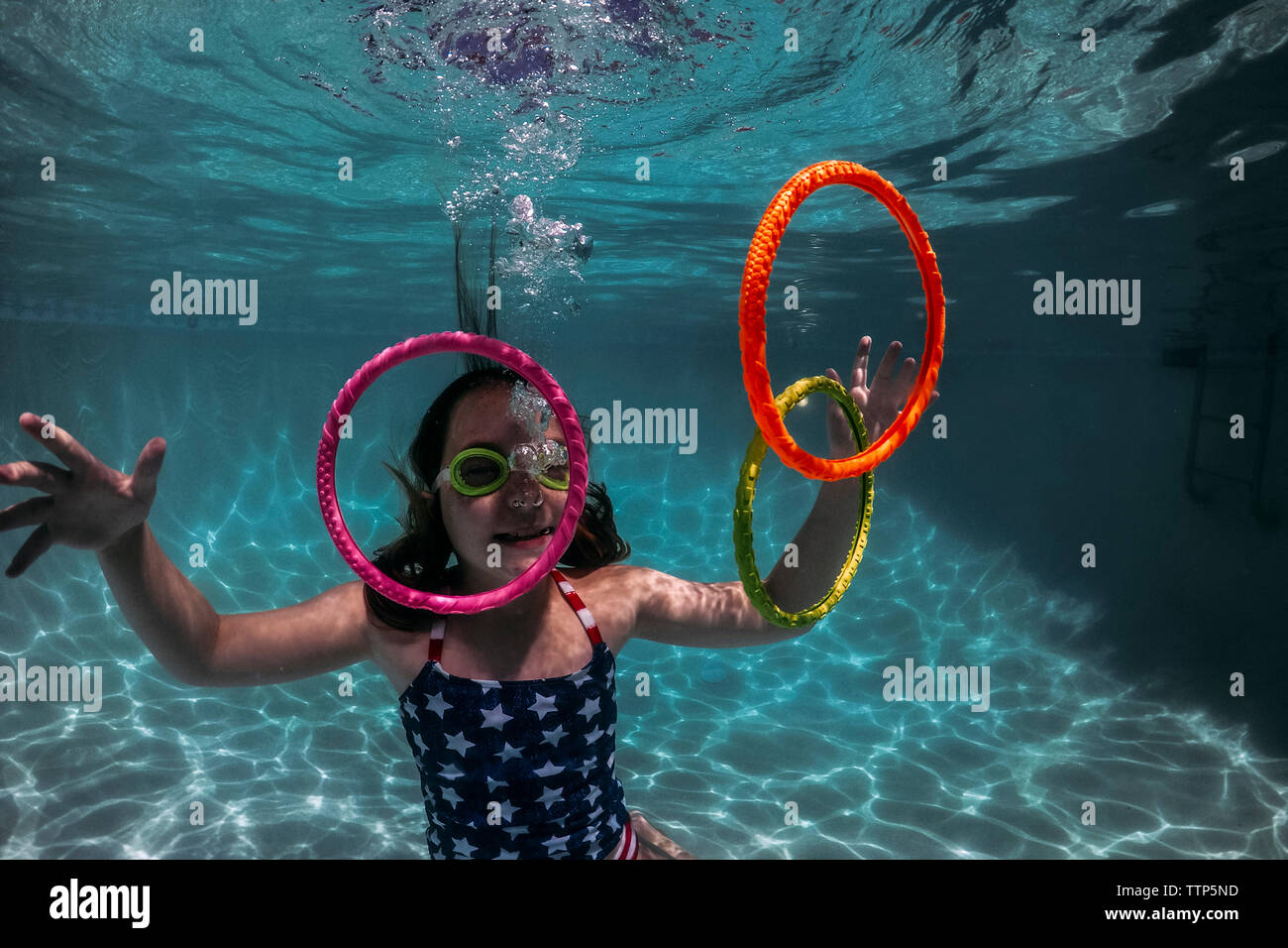 Smiling girl wearing swimming goggles while playing with colorful rings in pool Stock Photo
