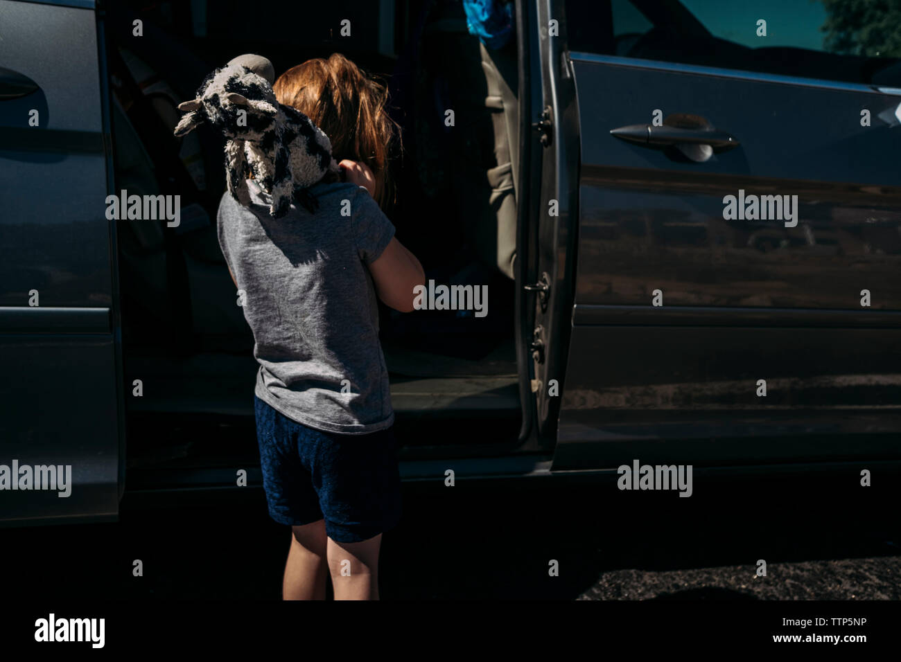 Rear view of girl carrying stuffed toy on shoulders while standing by car door during sunny day Stock Photo