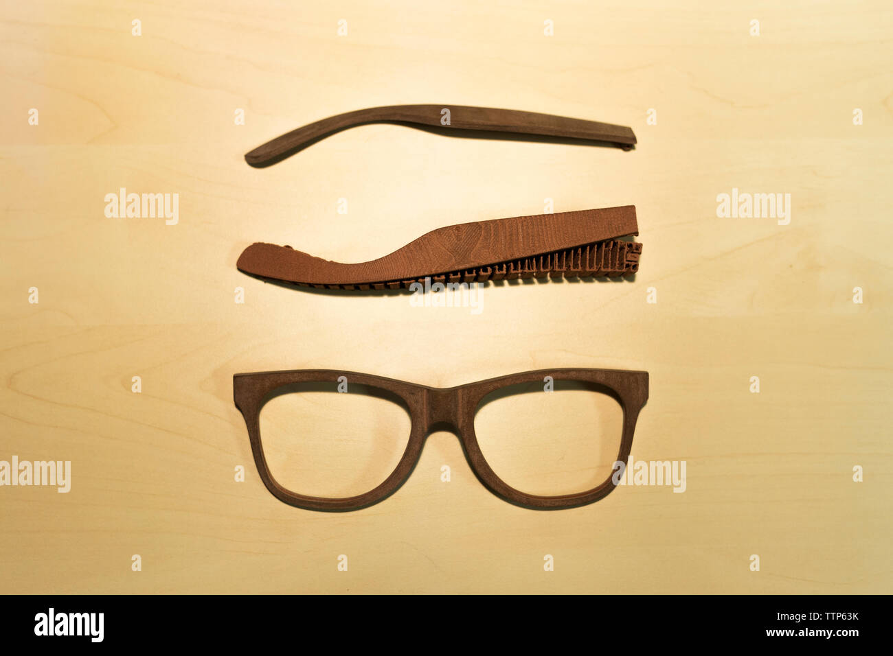Overhead view of disassembled 3-D glasses on wooden table in office - Stock Image