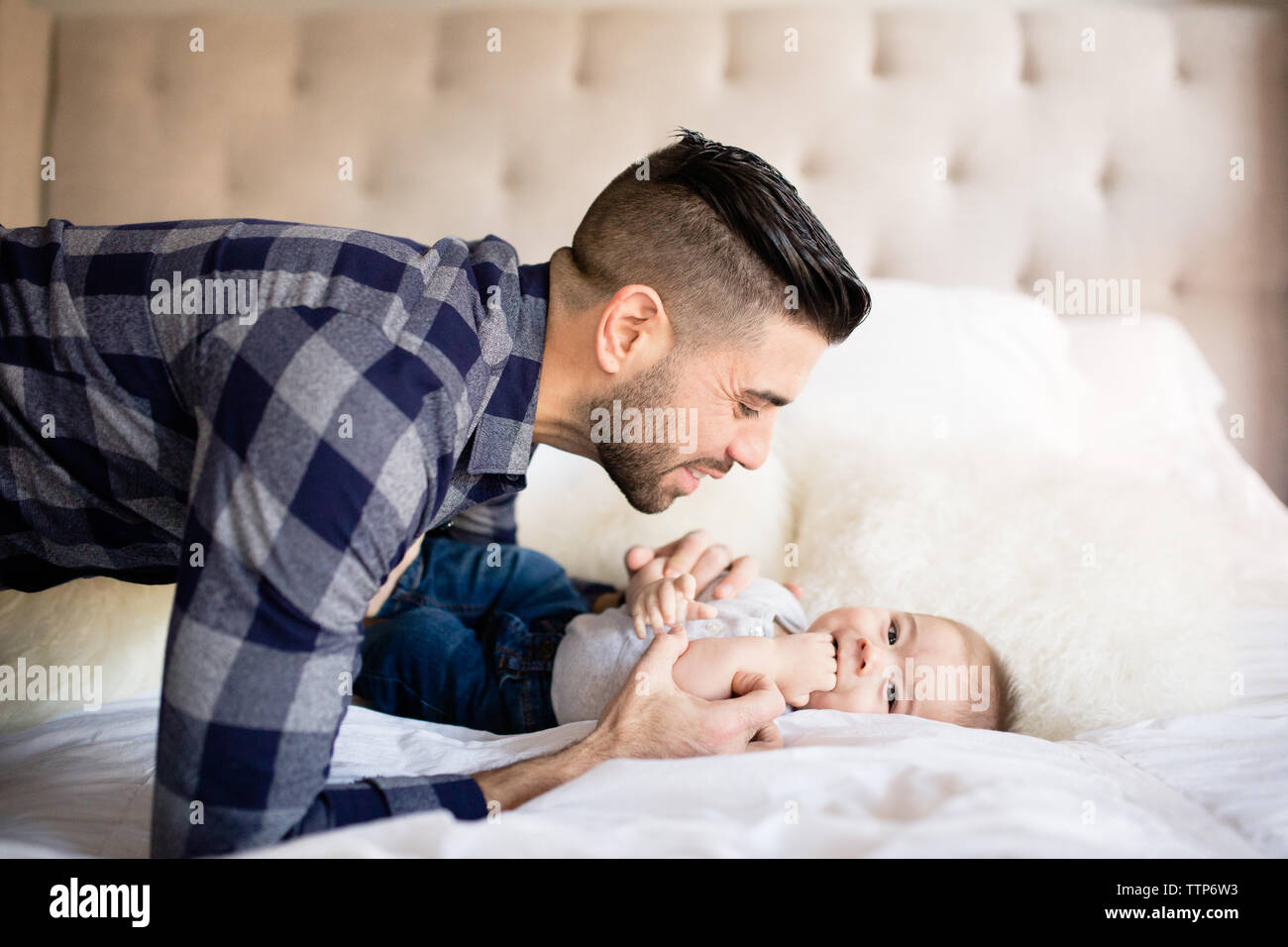 Side view dad looking at baby boy indoors Stock Photo