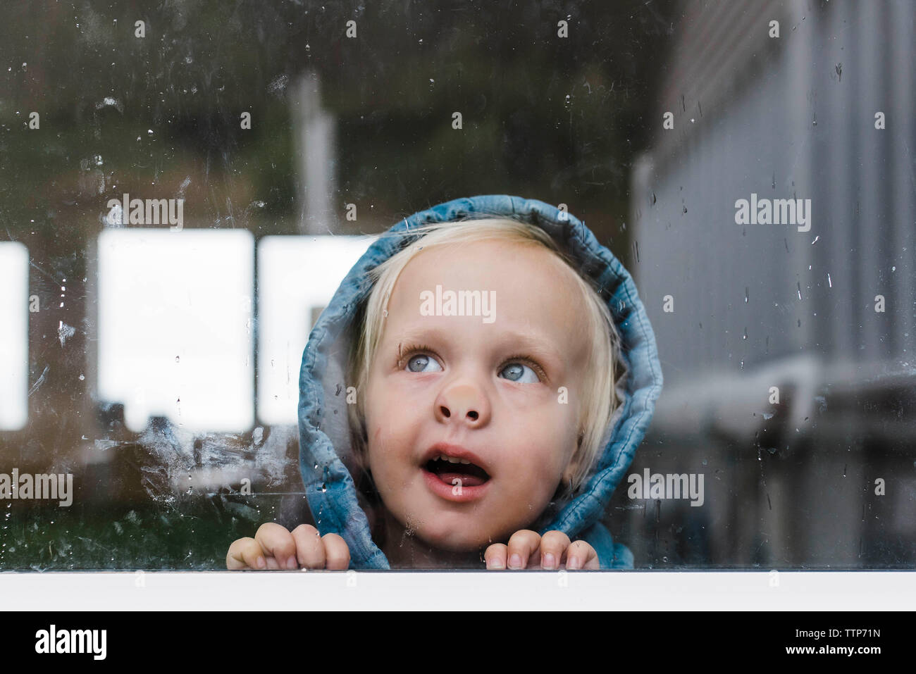 Close-up of girl looking through window seen through glass - Stock Image