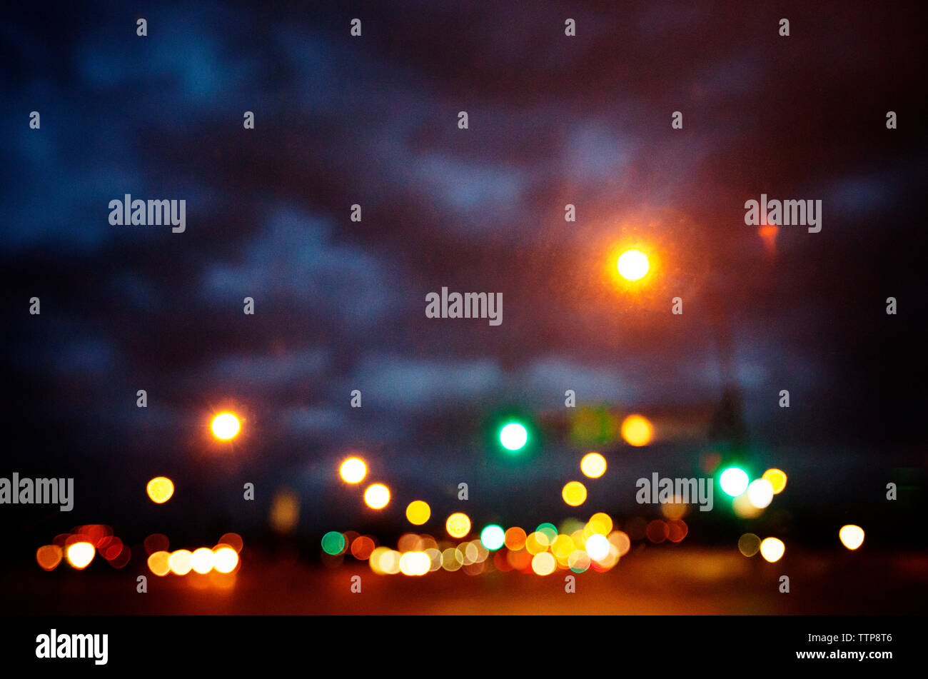 Illuminated street against cloudy sky - Stock Image