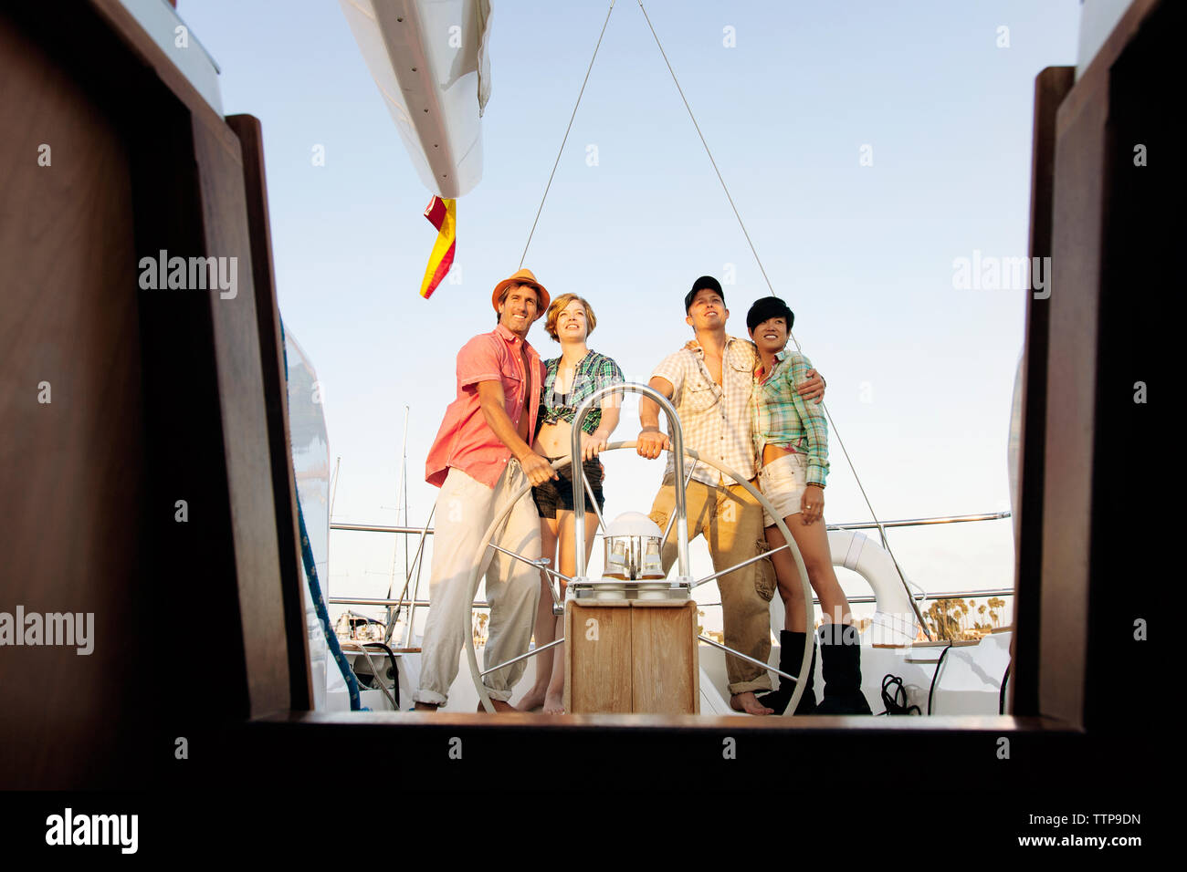 Happy couples standing by steering wheel on nautical vessel - Stock Image