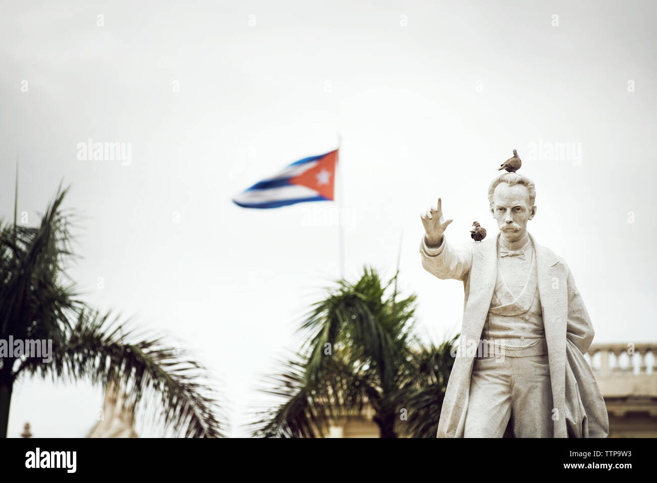 Birds perching on Jose Marti Statue against Cuban flag - Stock Image