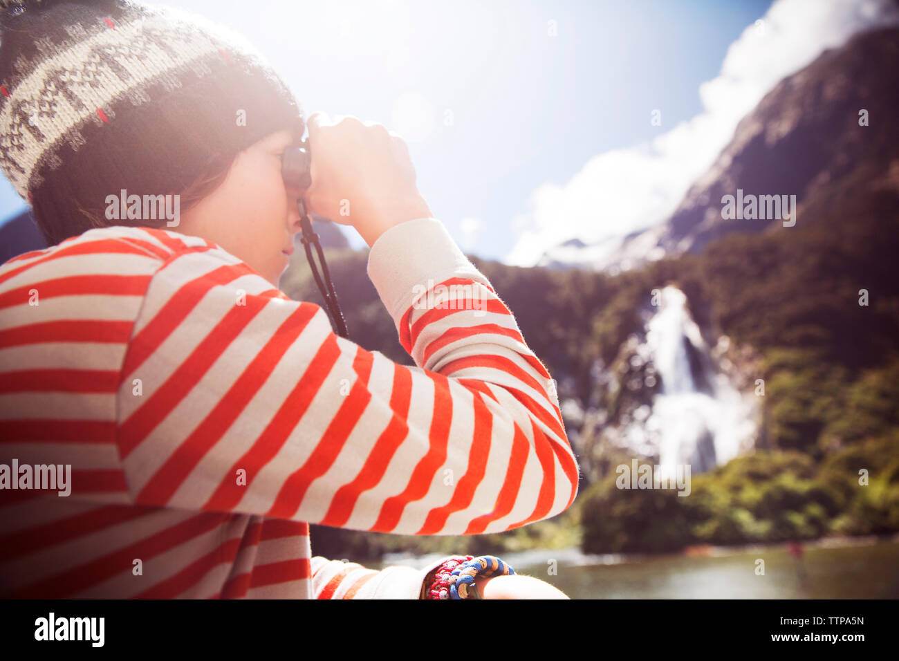 Side view of boy looking through binocular on sunny day - Stock Image