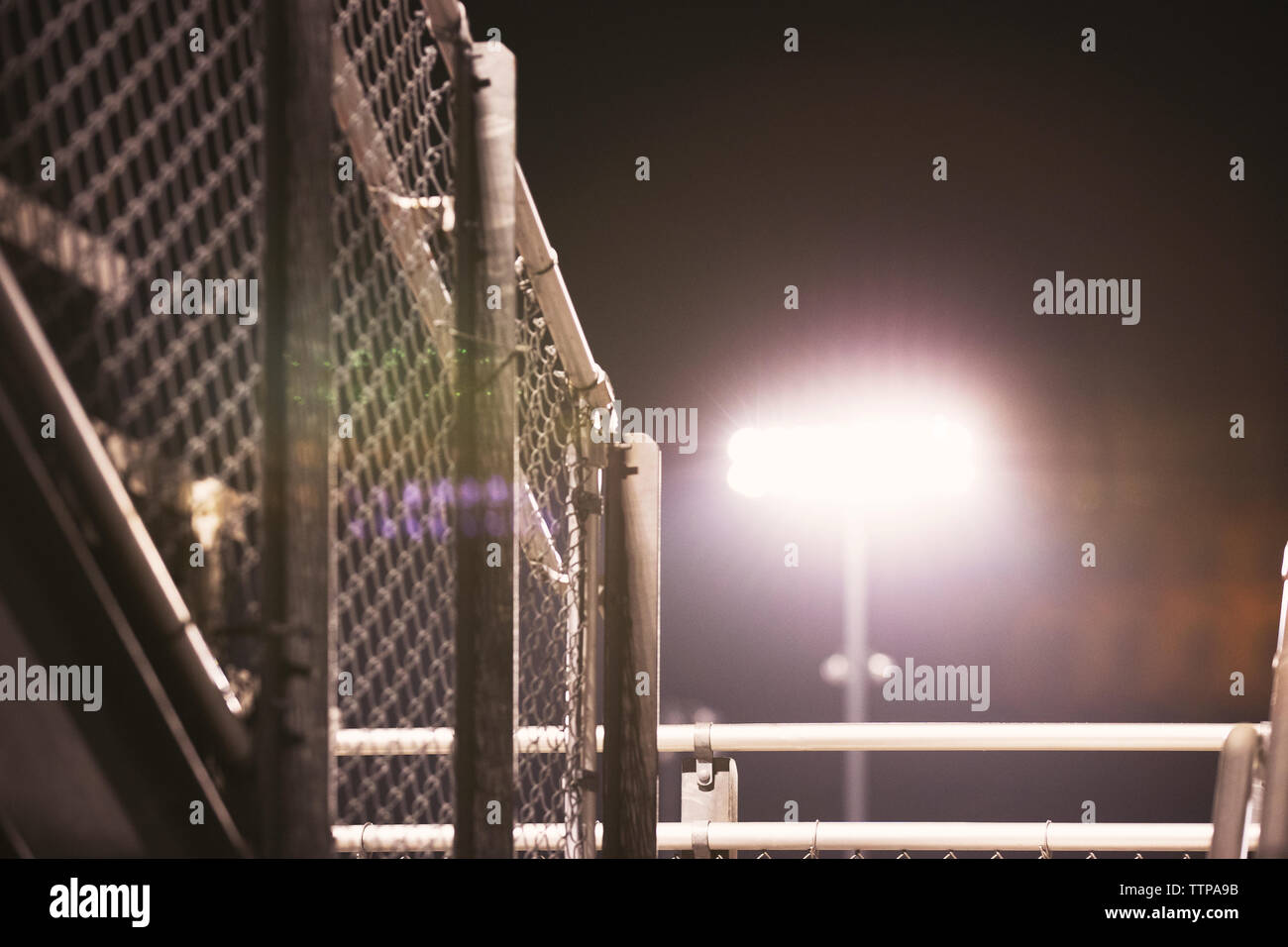 Low angle view of illuminated floodlight against sky at American football stadium - Stock Image