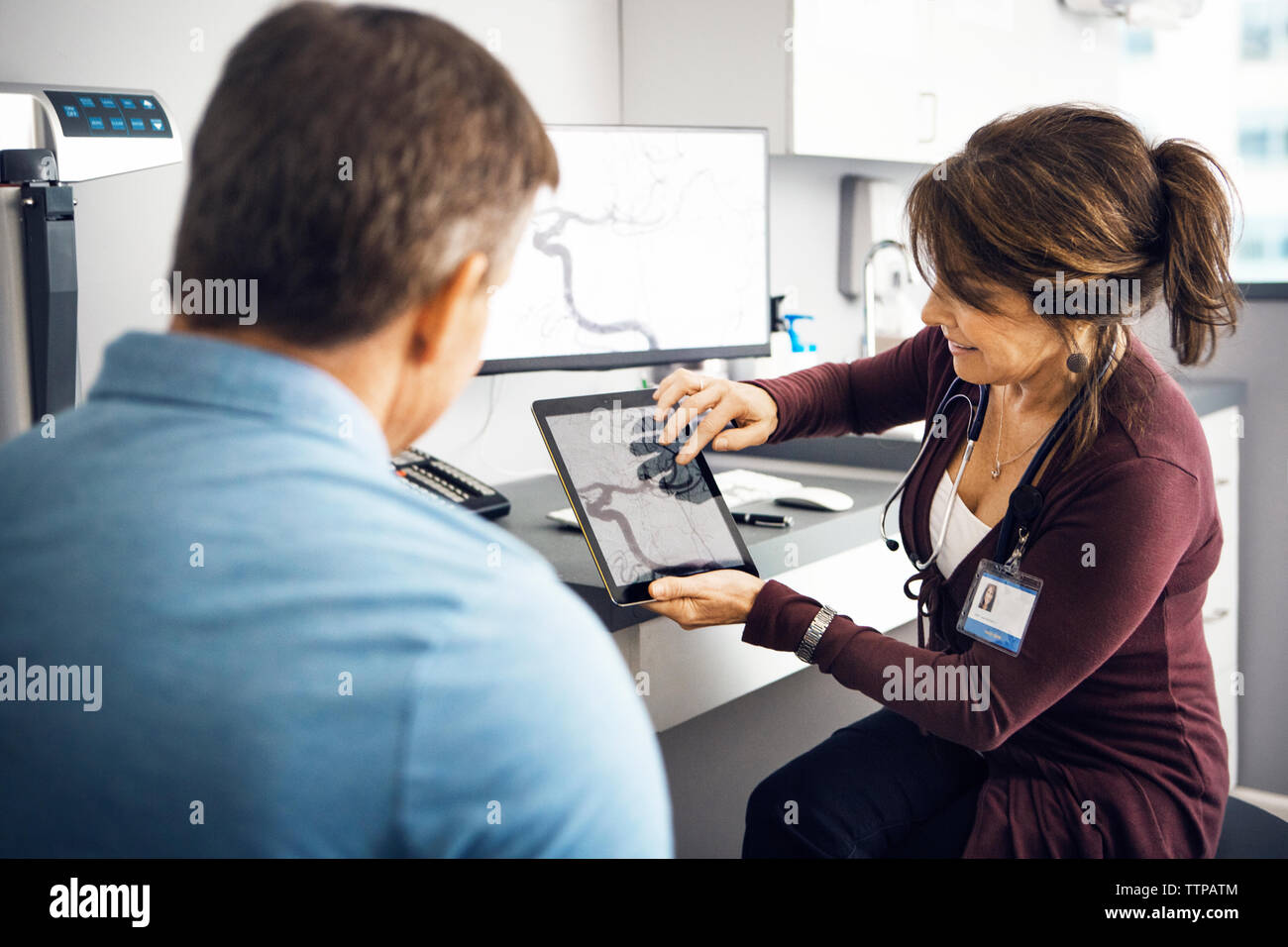 Female doctor explaining report to patient in clinic - Stock Image