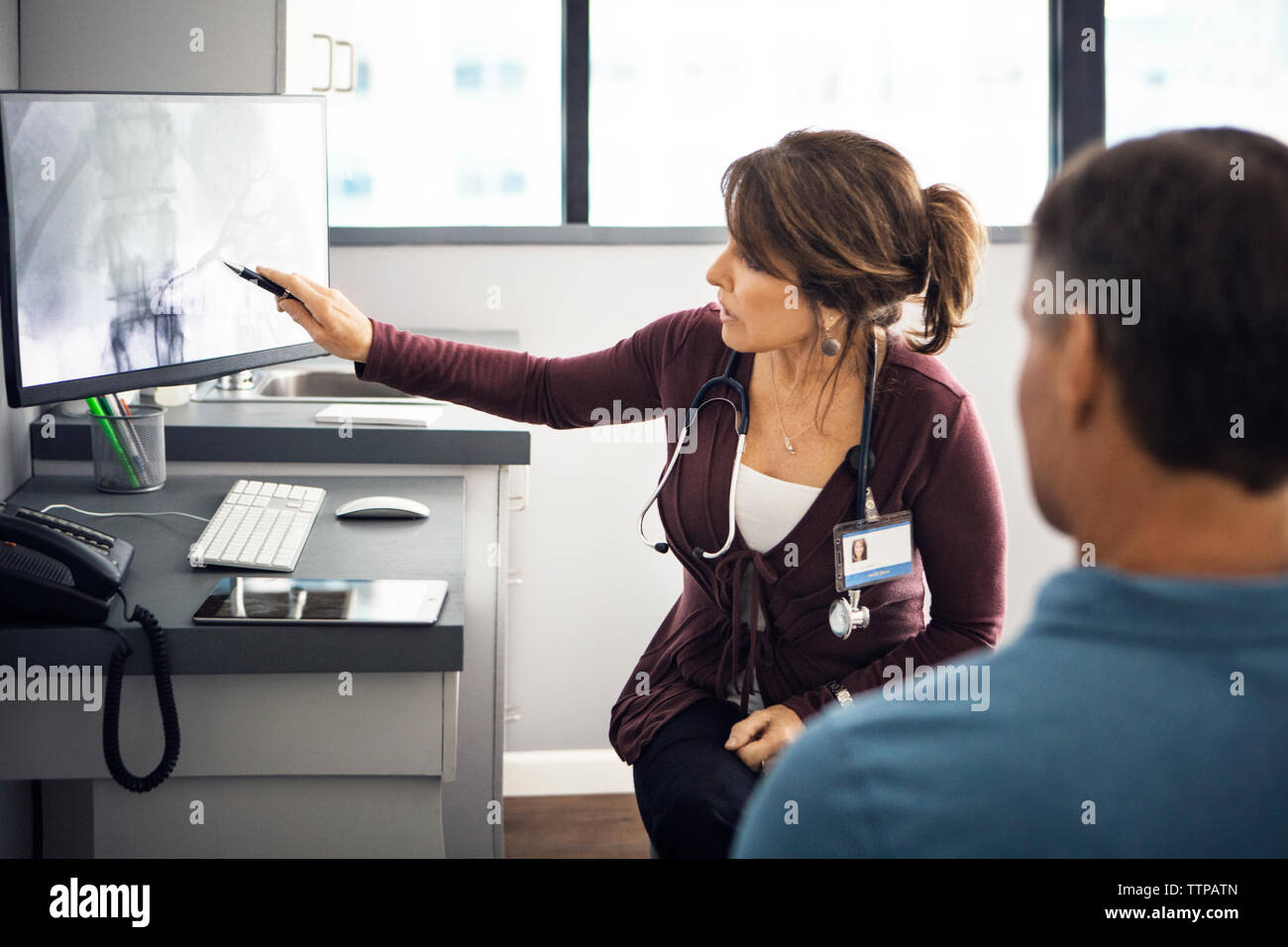 Female doctor explaining report to patient on computer in clinic - Stock Image