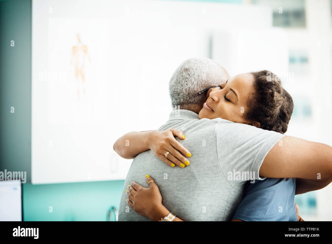Side view of female doctor embracing senior male patient in clinic - Stock Image