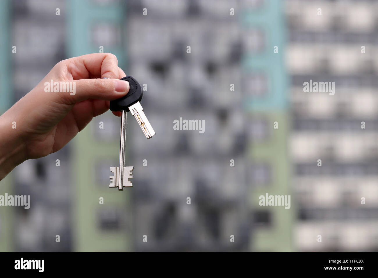 Real estate agent holding house keys on background of new residential building. Concept of house and apartment purchase, rental property - Stock Image