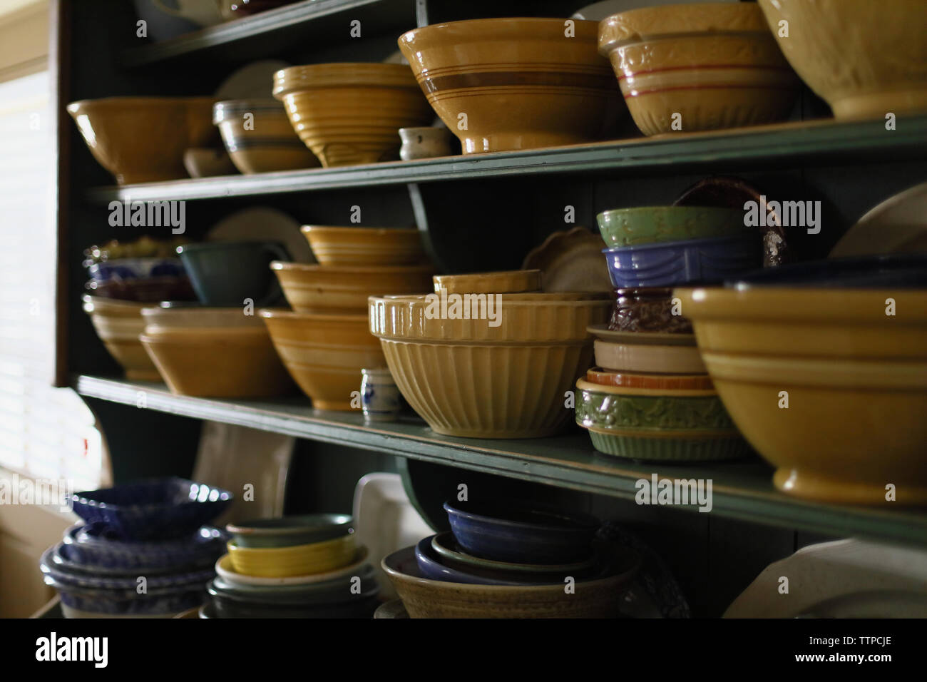 Various bowls arranged on shelves in kitchen Stock Photo