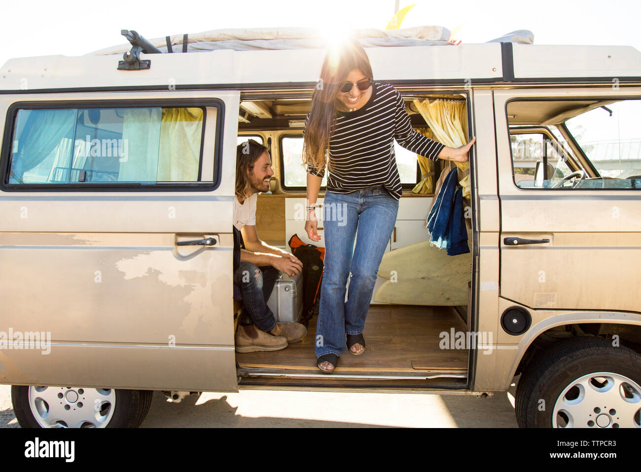 Happy woman disembarking mini van during vacation with man Stock Photo