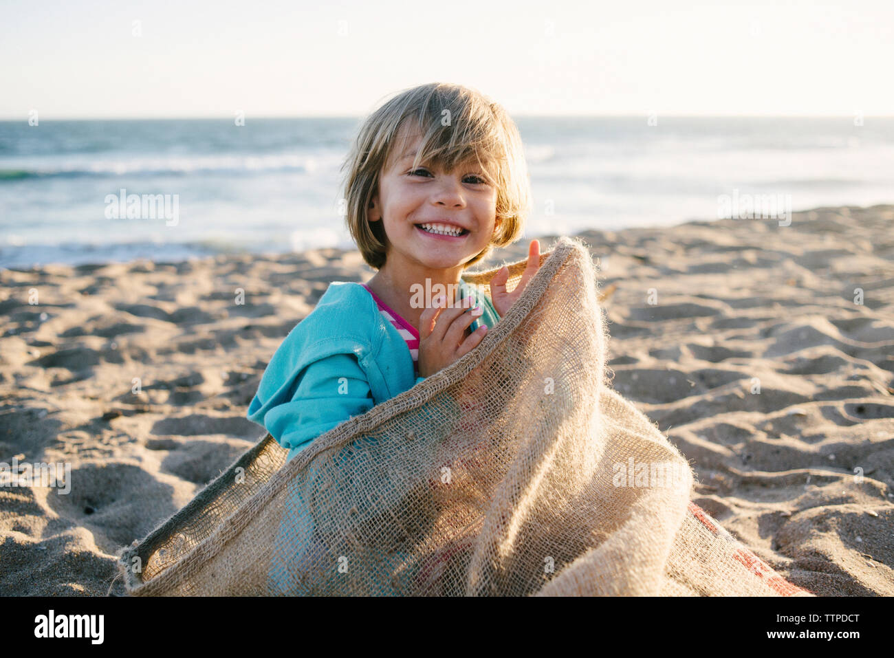 Portrait of girl sitting in sack at beach - Stock Image
