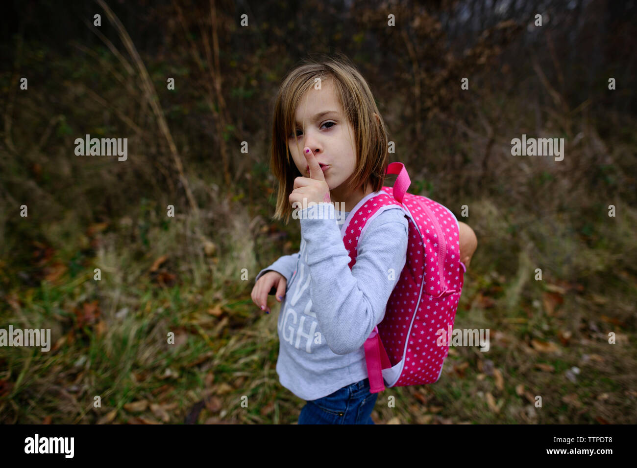 High angle portrait of girl with finger on lips standing on field - Stock Image