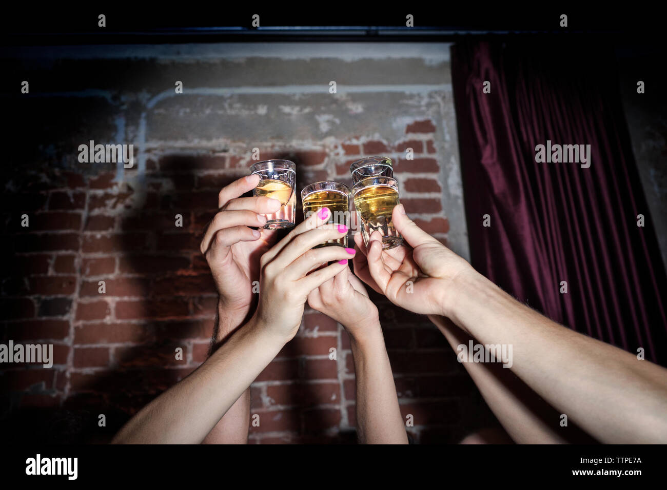 Cropped image of friends toasting tequila shots against brick wall - Stock Image