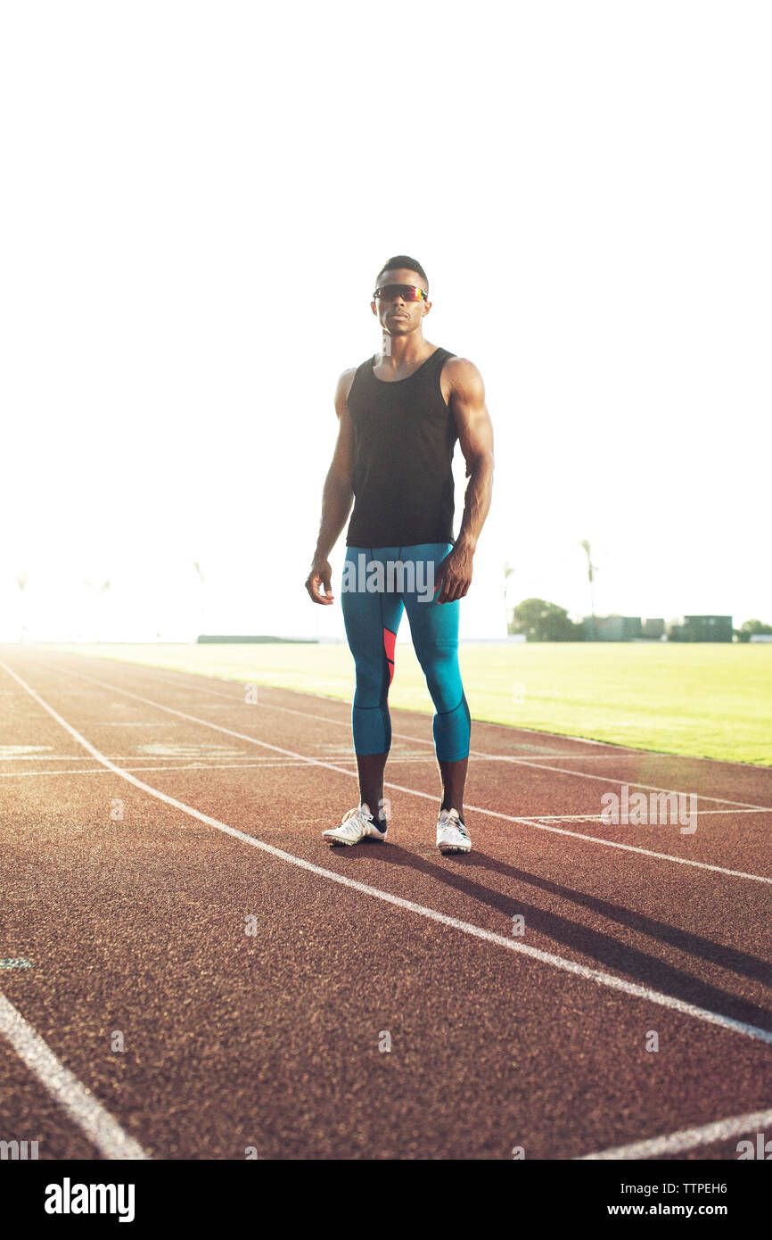 Portrait of confident male athlete standing on running tracks against clear sky Stock Photo