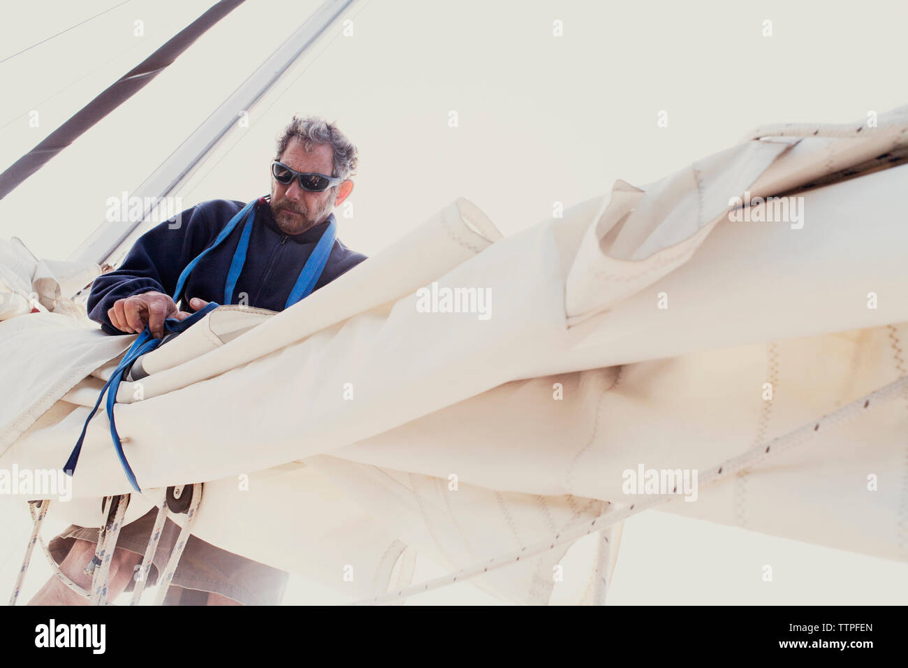 Low angle view of man tying sails of boat against clear sky - Stock Image