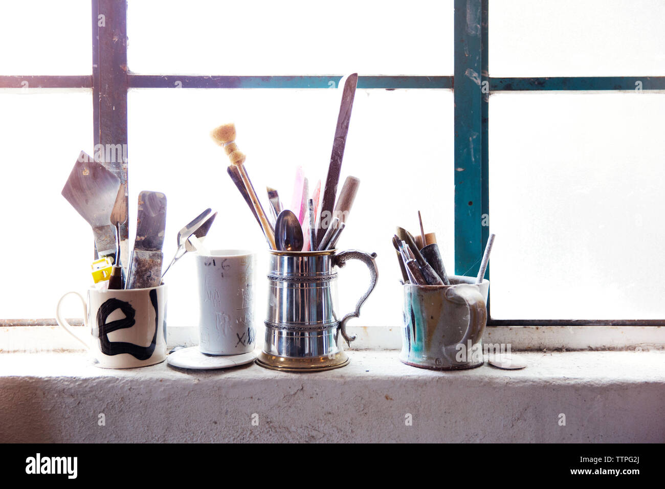Paint brushes and tools in cup on window sill Stock Photo